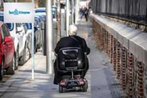 tekerlekli sandalyede giden yaşlı kadın