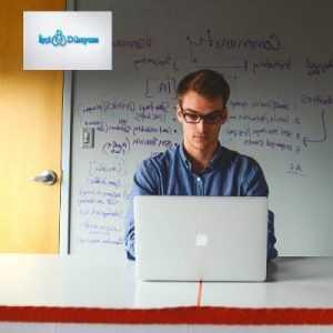 tahtanın önünde bilgisayara bakan gözlüklü erkek