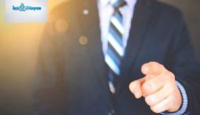 eliyle işaret yapan takım elbiseli adam